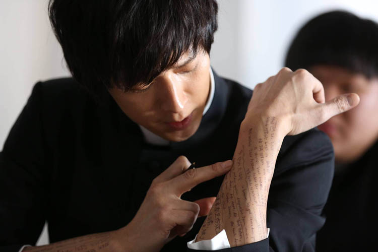 Kang Dong Won plays Deacon Choi in the Korean film The Priests. Here we can see him cheating on an exam. Tsk! I wonder how long it took the makeup person to write all that text on his arm? I bet there are many fan girls who would have done that job for free. (CJ Entertainment photo)