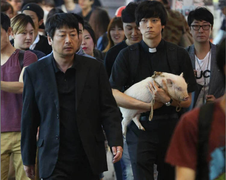 Kim Yun Seok, left, and Kang Dong Won in a scene from the Korean film The Priests. I wonder if those people are all extras, or if they are just regular folks walking down the street? Some of them do seem to be laughing - maybe because of the pig? (CJ Entertainment photo)